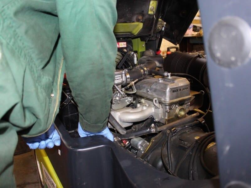 Mechanic working on Clark forklift engine